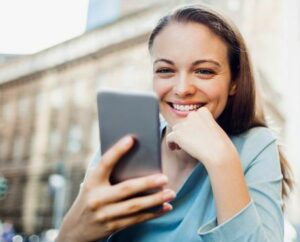 Close up of business woman using a phone while  drinking coffee